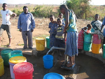 getting safe water from a hand pump installed by the Berega charity BREAD